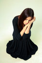 Sad woman in black dress sitting on the floor studio shot of a beautiful gray background Royalty Free Stock Photography