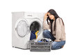 Sad woman emptying a washing machine seated on the floor isolated on white background Stock Photos