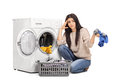 Sad woman emptying a washing machine studio shot of and looking at the camera isolated on white background Stock Image