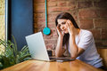Sad woman holding computer, laptop tablet screen looking surprised in coffee shop Royalty Free Stock Photo