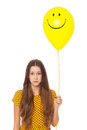 Sad woman holding smiley face balloon Royalty Free Stock Photo