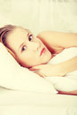 Sad woman lying in bed Royalty Free Stock Photography