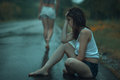 Sad woman in the rain a young girl sitting on road Royalty Free Stock Images