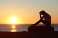 Sad woman silhouette worried on the beach at sunset with sun in background Royalty Free Stock Images
