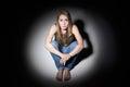 Sad Woman Sitting In Pool Of Light Royalty Free Stock Photo