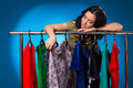 Sad Woman Under The Clothing Rack With Dresses
