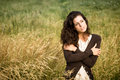 Sad woman walking in nature shivery brown sweater jacket hugging herself and field on late summer cold day sadness melancholia Stock Photo