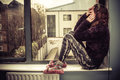 Sad woman by the window young is sitting on windowsill Royalty Free Stock Photos