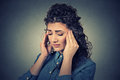 Sad woman with worried stressed face expression having headache closeup young isolated on gray wall background human emotions Stock Photos