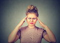 Sad woman with worried stressed face expression looking down trying to concentrate  on gray wall background Royalty Free Stock Photo