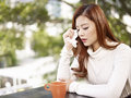 Sad woman young wiping tears with facial tissue Stock Image