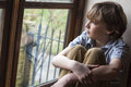 Sad young boy child looking out window sitting thinking and of rain covered Royalty Free Stock Photos