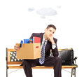 Sad young businessman with cloud over head holding box isolated on white background shot tilt and shift lens Stock Images
