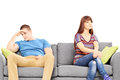 Sad young couple sitting on a sofa after an argument isolated white background Royalty Free Stock Photo