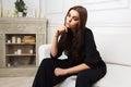 Sad young fashion woman in black jacket sitting on sofa Royalty Free Stock Photo