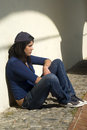 Sad young girl outdoors sitting against a wall Stock Image