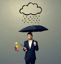Sad young man with black umbrella and drooped flowers standing under drawing storm cloud photo over grey background Royalty Free Stock Photography