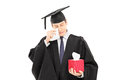 Sad young man in graduation gown holding box of wipes Royalty Free Stock Photos