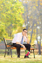 Sad young man holding a bouquet of flowers and sitting on bench wooden in park Stock Images