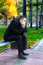 Sad young man sitting bench autumn park Stock Photos