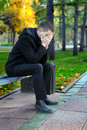 Sad young man sitting bench outdoor Royalty Free Stock Photos