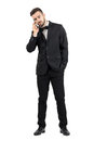 Sad young man in suit talking on the phone looking down full body length portrait isolated over white studio background Royalty Free Stock Photo