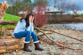 Sad young teen girl sitting on log along rocky beach by lake biracial in blue shirt and jeans Royalty Free Stock Images