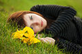 Sad young woman lying on the grass with a flowers Royalty Free Stock Image