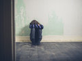 Sad young woman sitting on floor in empty room Royalty Free Stock Photo