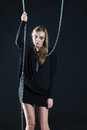 Sad zombie girl with black tears and cut throat hangs on chain Stock Photo
