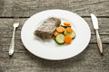Saddle of lamb with carrots and courgettes on a plate cover Stock Photos