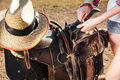 Saddle prepared for horse riding by young woman cowgirl Royalty Free Stock Photo