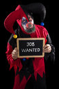 Sadly clown holding a slate with text job wanted, concept unempl Royalty Free Stock Photo