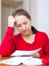 Sadness mature woman with bills at her home Stock Images