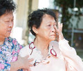 Sadness senior woman wiping off her tears women in eyes consoling by mature daughter natural outdoor park Stock Image