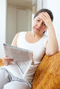 Sadness woman with newspaper mature at home Stock Images