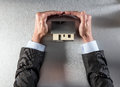 Safe insulation home with businessman hands protecting and securing roof Royalty Free Stock Photo