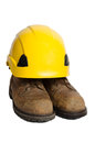 Safety boots and hard hat used leather yellow on white background Stock Photography