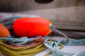 Safety buoy on ship bright red security rests gently reeled ropes ring board of the fishing boat Royalty Free Stock Image