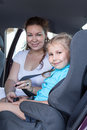 Safety children transportation with car seat in vehicle mother fastening daughter Stock Image