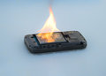Safety concept mobile phone battery explodes and burns due to overheat on blue background Stock Photos