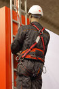 Safety harness worker on a ladder uses a to prevent falling from the building Royalty Free Stock Photos
