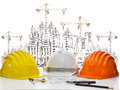 Safety helmet on engineer working table against sketching of building construction and high crane safety helmet on engineer workin