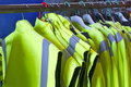 Safety jackets on hangers rail of with hiviz vest or tabards made of reflective yellow dayglo material Stock Images