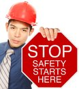 Safety starts here a man wearing a hardhat holding a stop sign with a message shallow depth of field Stock Photos