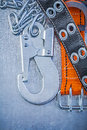 Safety strap metal chain carabiner hook on metallic background t Royalty Free Stock Photo
