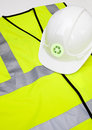 Safety vest and hard hat with recycling symbol over white background Royalty Free Stock Photo