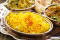 Saffron rice with indian curry as closeup on a silver tablet Stock Image