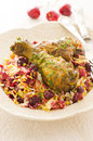 Saffron rice with sour cherries and chicken as closeup on a white plate Stock Photo