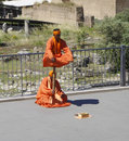 Saffron robe clad street performers robed turban perform a clever illusion of strength and meditation hoping for some coins to be Royalty Free Stock Photo